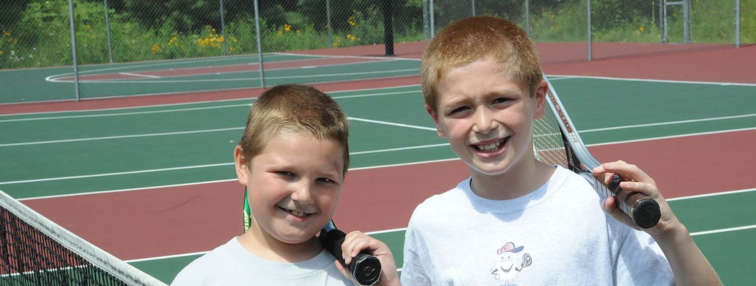 Children smiling and holding tennis rackets in hand at our tennis courts