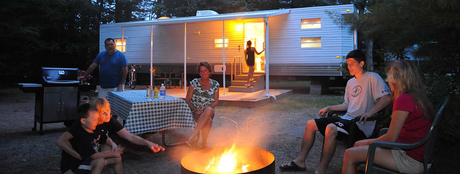 Family enjoying time by the fire in front of one of our RV rentals