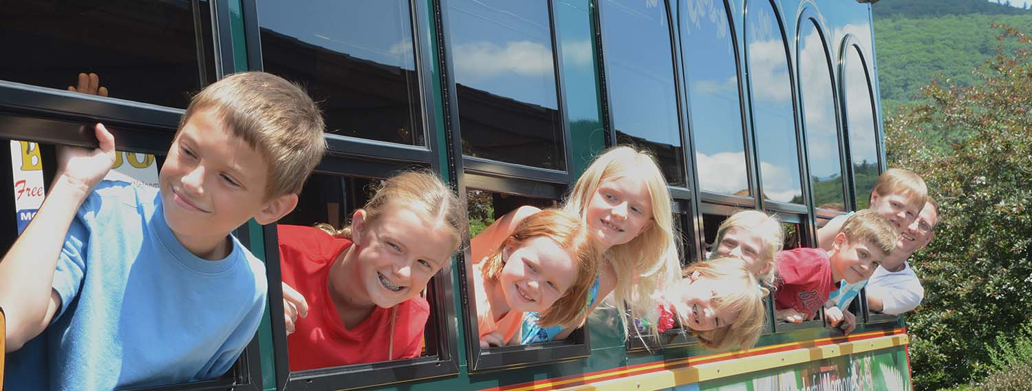 Children smiling looking out trolley windows