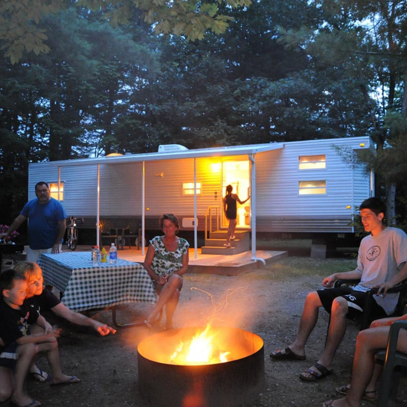Family enjoying time by the campfire in front of one of our RV rentals