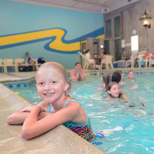 Child inside the indoor pool, holding onto the edge and smiling. In the background are other guests swimming