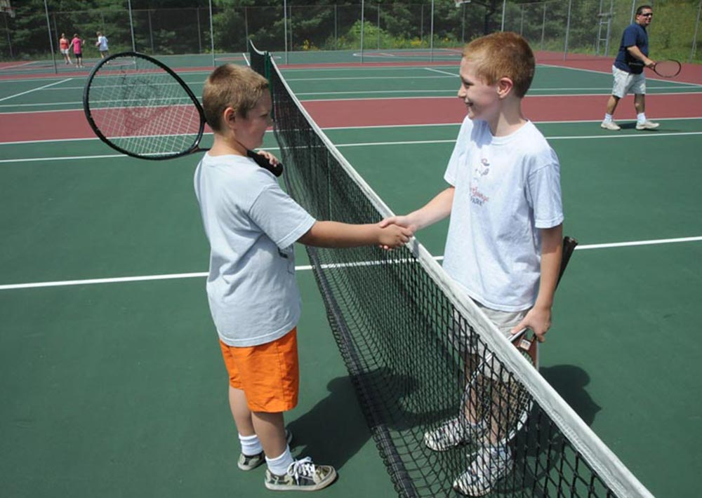 Children shaking hands on our tennis court