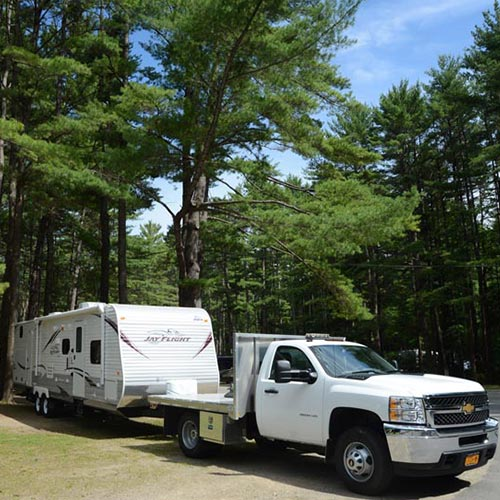RV trailer connected to truck, backing into campsite