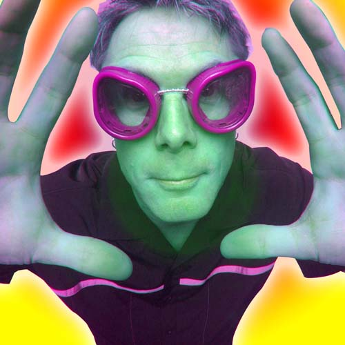 French Mountain Playhouse aritst, Mark Nizer wearing hot pink goggles and holding his hands up like hes looking through a fish bowl. There is a yellow background behind him.