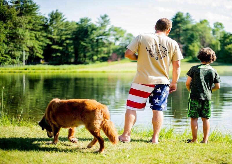 Man, boy, and dog at fishing pond