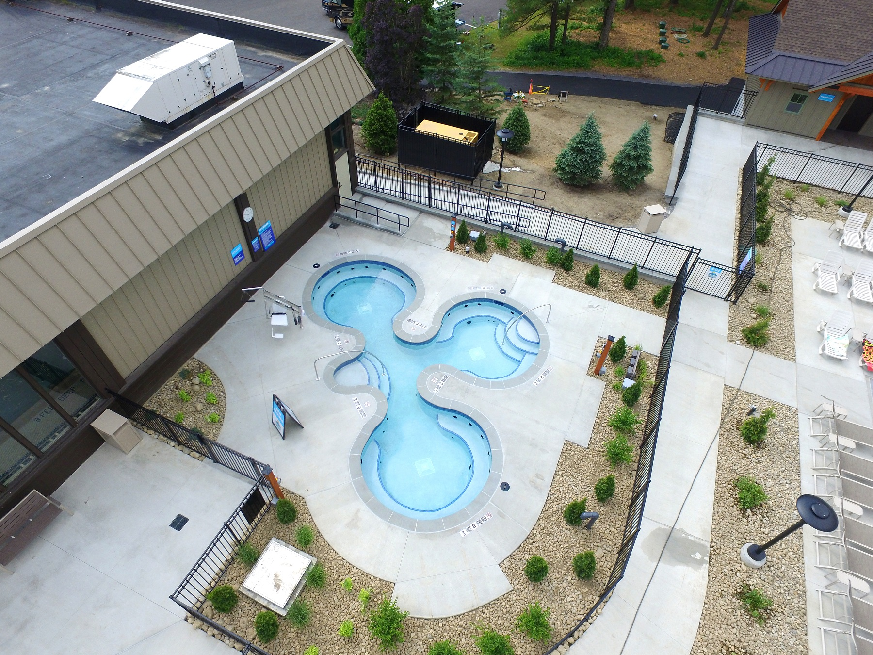 A birds eye view of Cascade Coves hottub area. 3 tubs are shown surrounded by a landscape area.