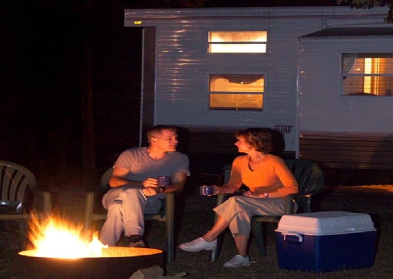 Couple sitting by fire with mugs outside of rental unit