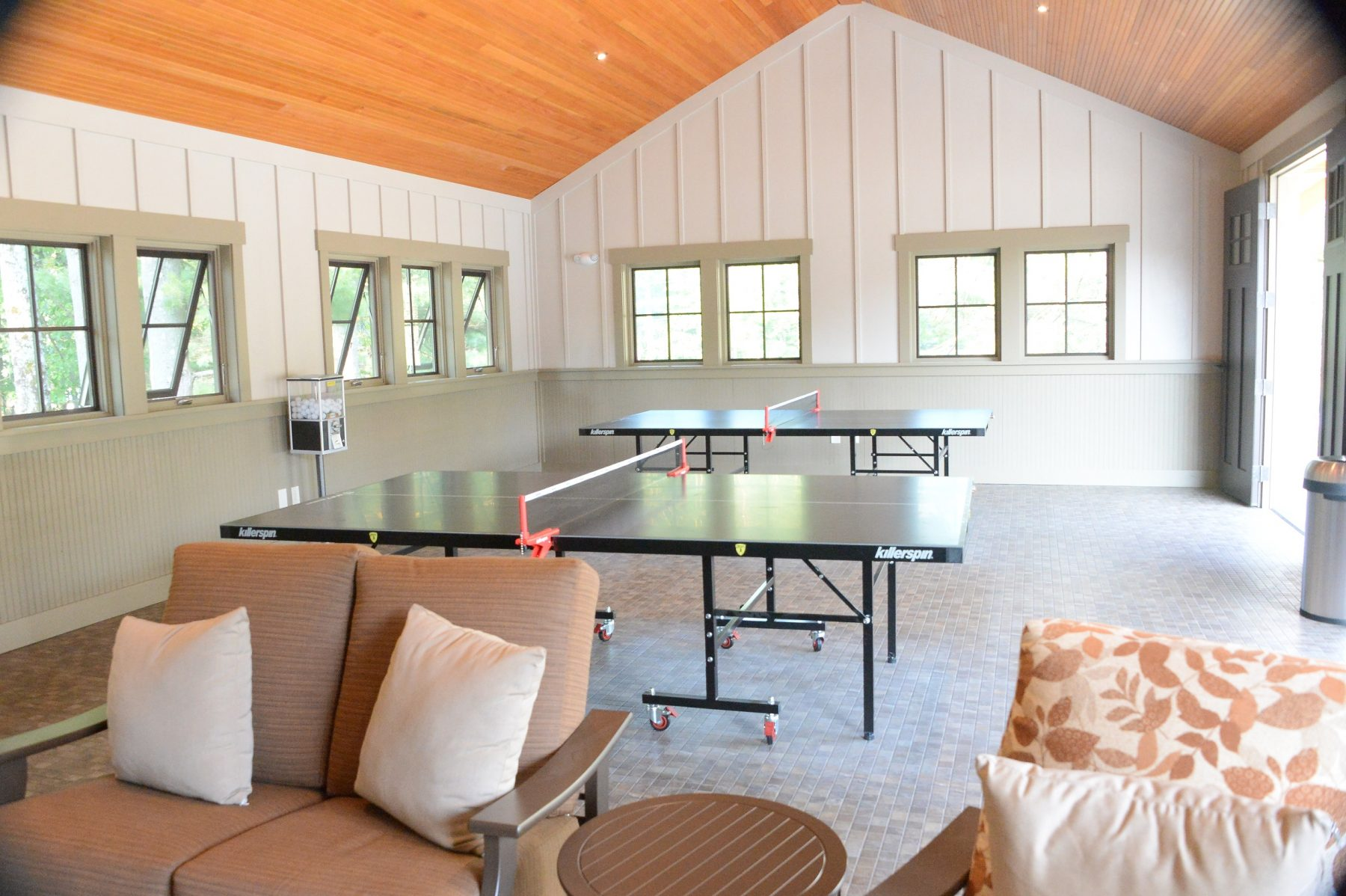 In the acitivty room there are two ping pong tables in the background of the photo with a ping pong ball dispenser located in between them to the far left. In the foreground of the photo there is a loveseat, a small circular table, and a chair for guests to lounge in.