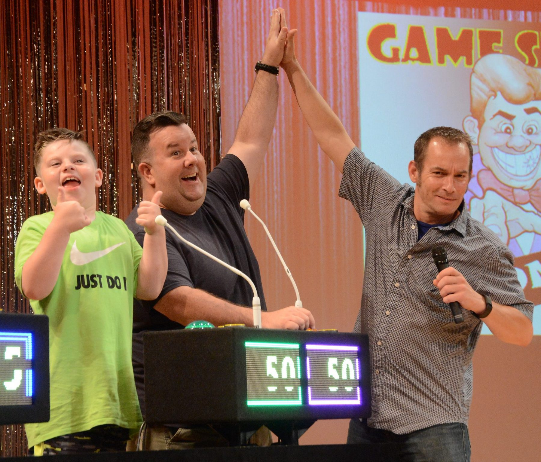 Game show madness night at the French Mountain Playhouse. The host to the right is high fiving a gentleman who is wearing a dark grey shirt and smiling. Next to him is a younger boy in a lime green t shirt smiling and giving two thumbs up! In front of them are microphones, and their score boards which shows 50 points each in green and purple lights. To the left is another score board showing 25 points.
