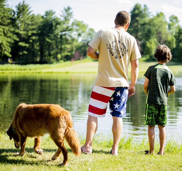 Father and son with dog fishing in pond