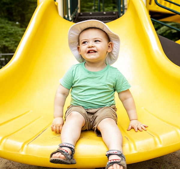 Toddler sitting on the end of yellow slide