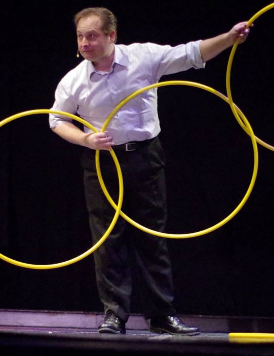 Illusionist David Garrity with 3 connected hoola hoops on stage with a head set microphone
