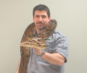 Bingo Pavilion artists, Mark Perpetua with an anaconda sitting on his shoulders.