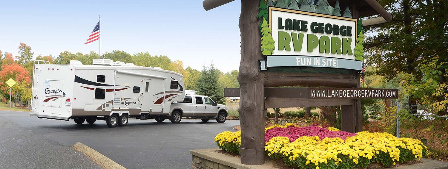 RV Park entrance sign with rv driving in