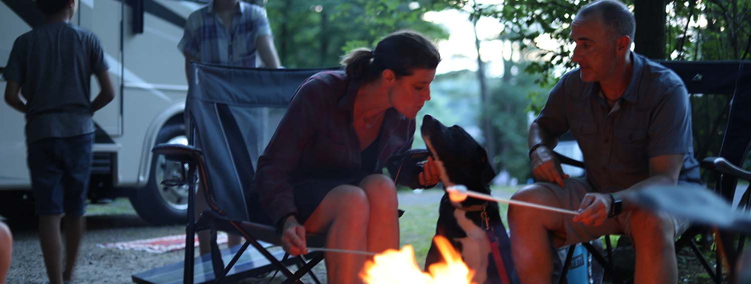 Women with dog around campfire