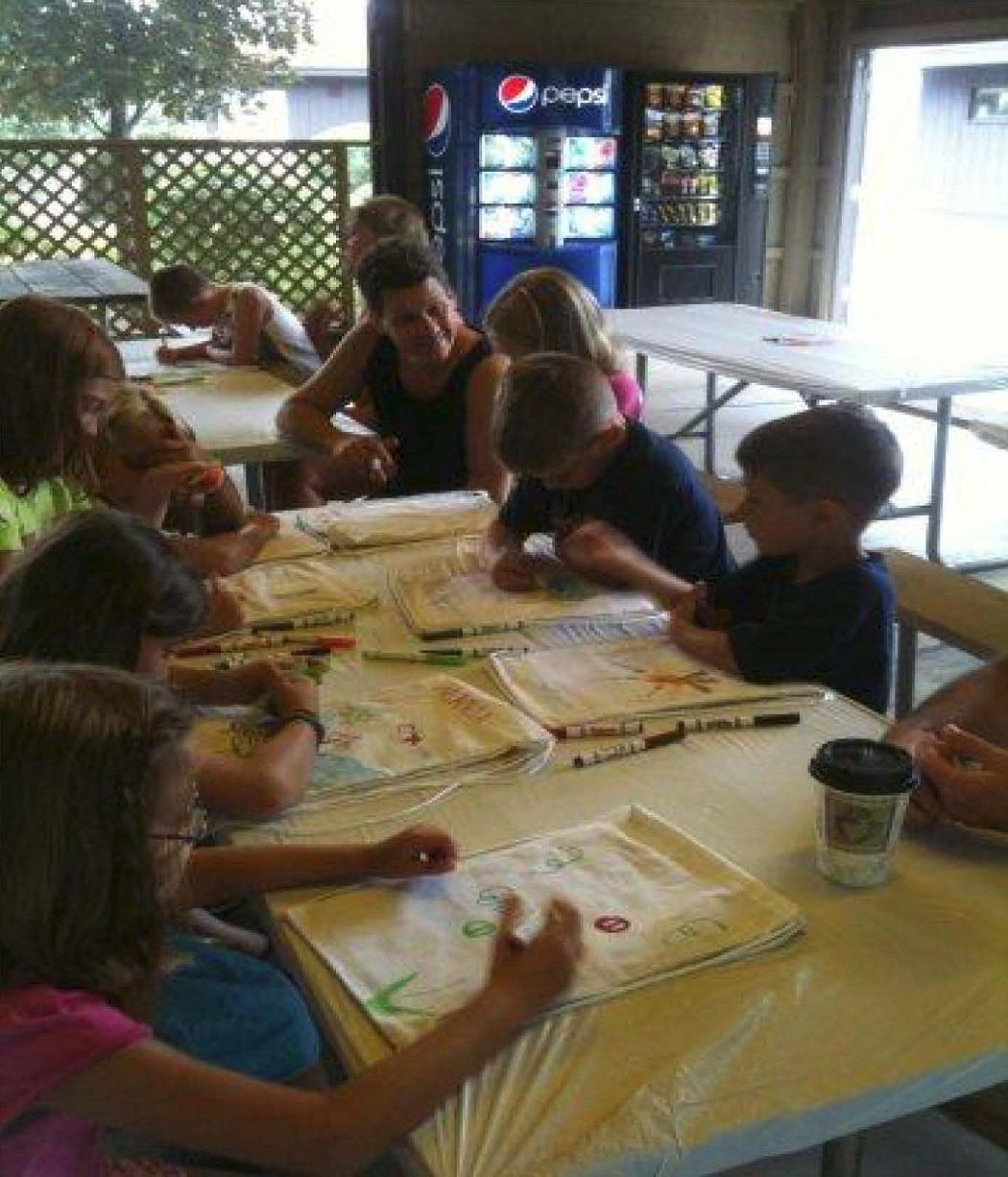 Numerous guests sitting in the Bingo Pavilion coloring on white draw string backpacks for the day's hands on activity project.