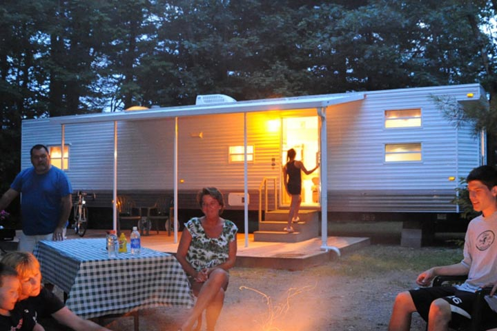 Family gathered outside camping trailer