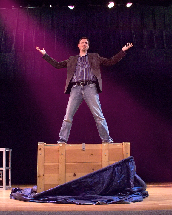 French Mountain Playhouse artist, Michael Mills standing on top of a wooden chest with his arms raised. There is a blue curtain that is partially covering the chest.